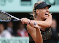 Russia&#39;s Maria Sharapova hits a return to Italy&#39;s Sara Errani during their final French Open match. Sharapova won 6-3, 6-2 to complete the career Grand Slam
