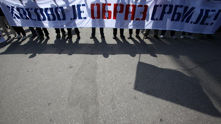 "Protesters carrying a banner that reads: ""Kosovo is Serbia's honor!"" during the protest of Serbian nationalist organization Dveri, in Belgrade, Serbia, Sunday, April 21, 2013. Several hundred protesters gathered to protest against the recognition of Kosovo as an independent state. (AP Photo/Darko Vojinovic)"