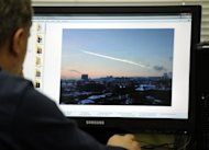 <p>A man in Moscow looks at a computer screen displaying a picture reportedly taken in the city of Chelyabinsk, on February 15, 2013, showing the trail of a falling object above a residential area of the city.</p>
