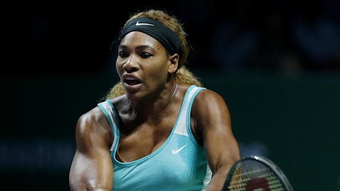 Serena Williams of the U.S. makes a backhand return to Denmark's Caroline Wozniacki during their semifinal match at the WTA tennis finals in Singapore, Saturday, Oct. 25, 2014. (AP Photo/Mark Baker)