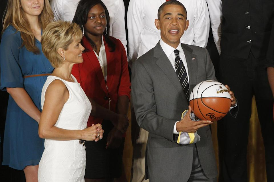 President Barack Obama stands with head coach Kim Mulkey as he is presented with a jersey and a basketball at a ceremony honoring the 2012 NCAA Women's basketball champions Baylor University Bears in the East Room at the White House in Washington, Wednesday, July 18, 2012. (AP Photo/Charles Dharapak)