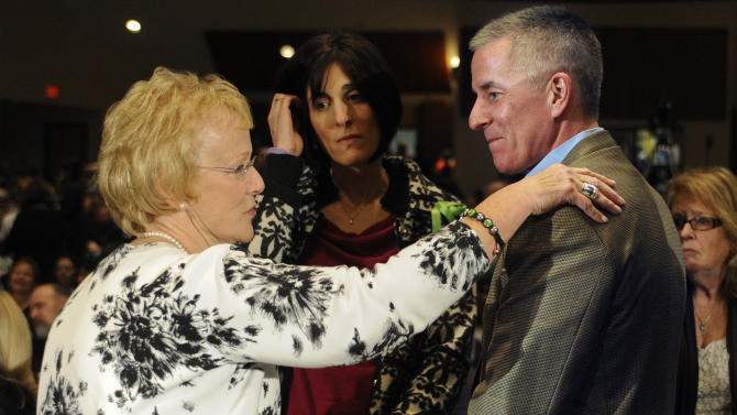 Newtown First Selectman Pat Llodra, left, touches, Chris McDonnell, father of Sandy Hook Elementary School shooting victim Grace McDonnell, right, at a hearing of a legislative task force on gun violence and children's safety at Newtown High School in Newtown, Conn., Wednesday, Jan. 30, 2013. Connecticut lawmakers are in Newtown for the hearing, where those invited to give testimony include first responders and families with children enrolled at Sandy Hook Elementary. (AP Photo/Jessica Hill)