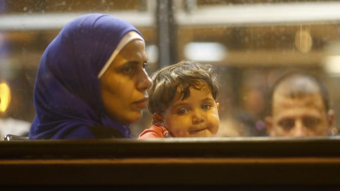 A mother and her child sit in a bus, which is supposed to leave to Austria and Germany, at the Keleti trainstation in Budapest