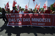 "Participants of a May Day march organized by the German trade union carry flags and banners as they march through Berlin, Germany, Sunday, May 1, 2011. Banner in front reads: "" This is the least, fair salaries, fair jobs""."