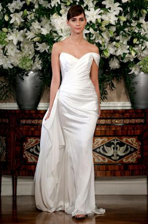 This March 2013 photo released by Romona Keveza shows a sleeveless Romona Keveza Coutour wedding dress. The traditional bridal gown isn't a skimpy silhouette: It's long and typically without a plunging neckline or high slit. There's often a whole lot of fabric. One of the few opportunities for brides to be a little bare is to go with a strapless or sleeveless dress. New bridal collections are dominated by dresses with no sleeves.  (AP Photo/Romona Keveza)