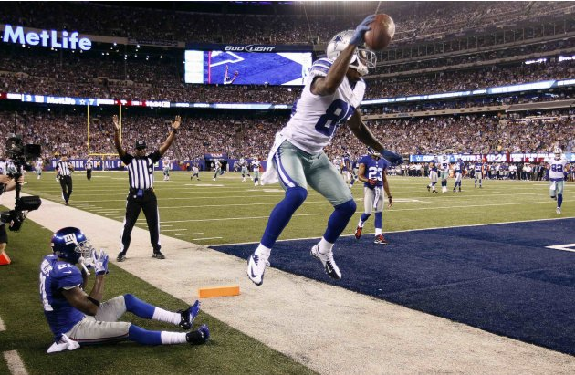 Cowboys receiver Kevin Ogletree celebrates his second touchdown of the game as New York Giants' Kenny Phillips sits on the ground during their NFL football game in East Rutherford