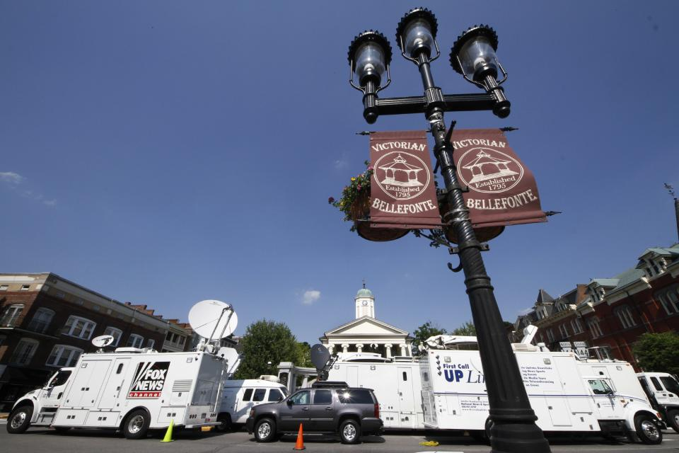 Television satellite trucks line South Allegheny Street in front of the Centre County Courthouse in Bellefonte, Pa.,  Sunday, June 10, 2012 in preparation for opening statements in the child sexual abuse trial of former Penn State Football assistant football coach Jerry Sandusky on Monday morning. (AP Photo/Gene J. Puskar)