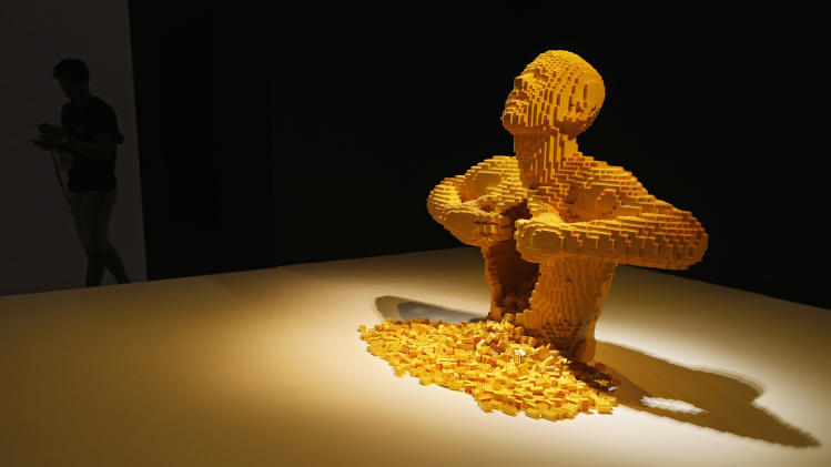 "Visitor walks past ""Yellow"" during the media preview of The Art of the Brick exhibition in Singapore"