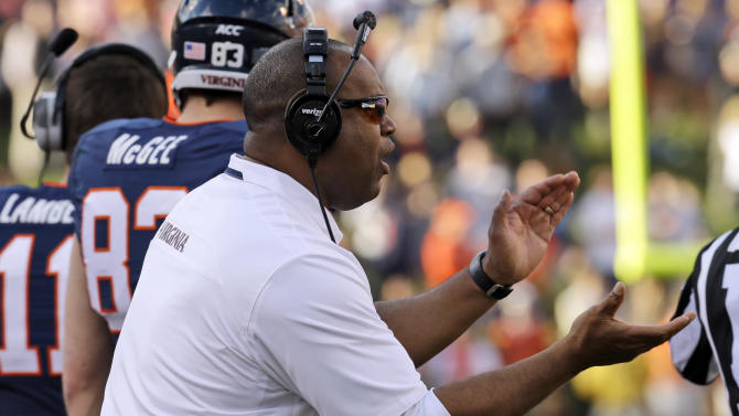 Virginia head coach Mike London cheers his team during the first half of an NCAA college football game against Clemson in Charlottesville, Va., Saturday, Nov. 2, 2013. (AP Photo/Steve Helber)