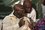 <p>Ghana opposition presidential candidate Nana Akufo-Addo talks to an aide during press conference in Accra on December 28, 2012. Ghana's main opposition, alleging electoral fraud, filed a court challenge today to results from this month's presidential polls handing victory to incumbent John Dramani Mahama.</p>