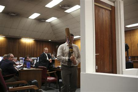 A policeman demonstrates the effect of hitting of bathroom door with cricket bat during trial of Oscar Pistorius in North Gauteng High Court in Pretoria