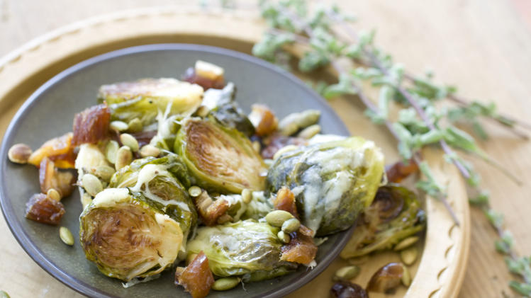 This Oct. 14, 2013 photo shows Gruyere roasted brussels sprouts with pepitas and dates in Concord, N.H. (AP Photo/Matthew Mead)
