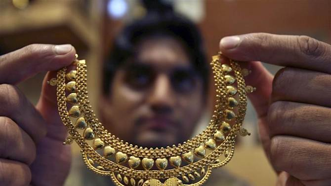 A salesman poses with gold necklace at a jewellery shop in Jammu