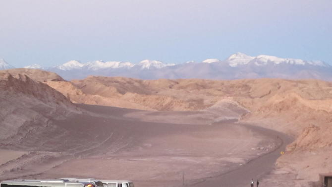 This August 2012 photo shows tour buses waiting for visitors to return from watching the sunset over the desolate Valle de la Luna (Moon Valley) in Chile's Atacama Desert. After watching the sun sink in the  west, spectators are then treated to a second glowing sky over the Andes. (AP Photo/Karen Schwartz)