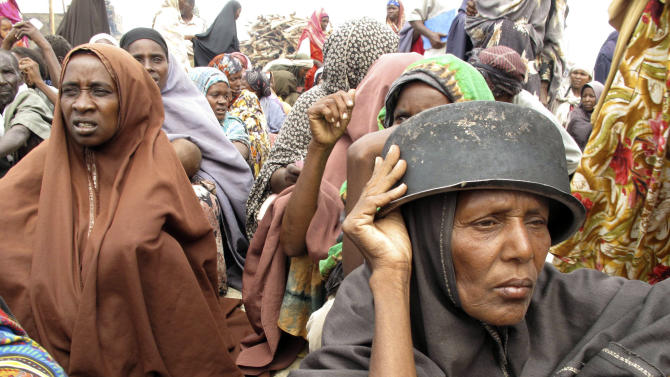Somalis displaced by famine wait to receive rations at a displaced camp in Mogadishu, Somalia, Monday, July 25, 2011. Some thousands of people have arrived in Mogadishu seeking aid and The World Food Program executive director Josette Sheeran said Saturday they can't reach the estimated 2.2 million Somalis in desperate need of aid who are in militant-controlled areas of Somalia.(AP Photo/Mohamed Sheikh Nor)