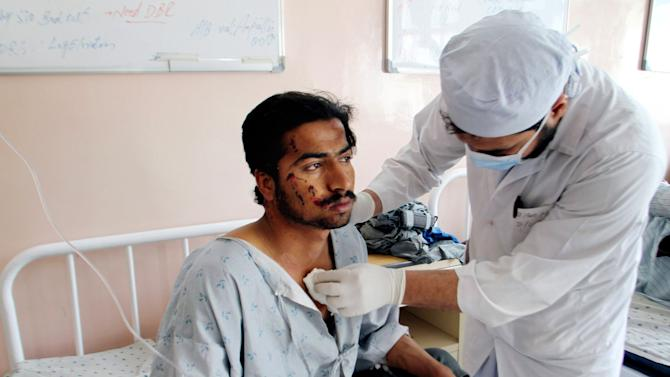 An Afghan doctor treats a wounded man at a hospital in Kandahar, south of Kabul, Afghanistan, Sunday, Jan. 27, 2013. A police truck packed with officers and detainees struck a roadside bomb in southern Afghanistan's largest city, killing several of those aboard, officials said Sunday. (AP Photo/Allauddin Khan)