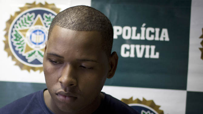 Wallace Aparecido Souza Silva is presented to the press at Special Police Unit for Tourism Support (DEAT) after being arrested for allegedly attacking tourists in Rio de Janeiro, Brazil, Tuesday, April 2, 2013. An American woman was gang raped and beaten aboard a public transport van while her French boyfriend was shackled, hit with a crowbar and forced to watch the attacks after the pair boarded the vehicle in Rio de Janeiro's showcase Copacabana beach neighborhood, police said.  The attacks took place over six hours starting shortly after midnight on Saturday. (AP Photo/Felipe Dana)