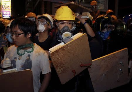 A protester carries a wooden board during a confrontation with riot police at Mong Kok shopping district in Hong Kong