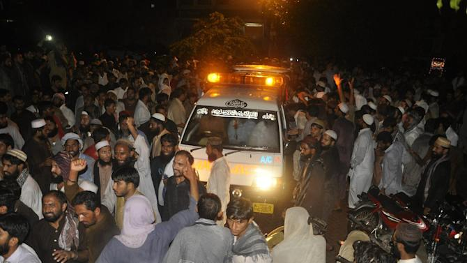 People attend funeral procession of the Sunni militant leader Malik Ishaq and others in their hometown of Rahimyar Khan, Pakistan, Wednesday, July 29, 2015. Ishaq, one of Pakistan's most-feared Islamic militant leaders, believed to be behind the killing of scores of minority Shiites, was gunned down along with 13 associates during a militant assault on a police convoy that was transporting him from prison on Wednesday. (AP Photo/Siddique Baluch)