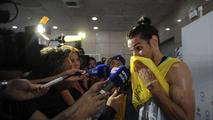 PSG's Cavani talks to media after a training session in Beijing