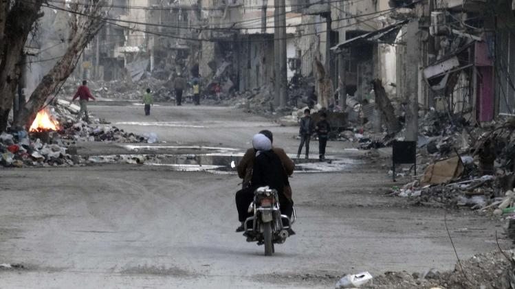 A man and a woman ride a motorcycle along a street filled with debris of damaged buildings in Deir al-Zor