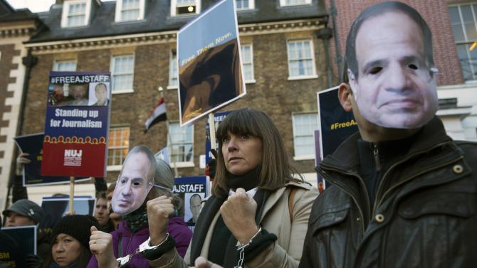 Protesters demonstrate for the release of Al Jazeera journalists outside the Egyptian Embassy in London