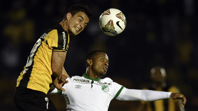 Diogo of Uruguay's Penarol, left, heads the ball with Luis Mosquera of Colombia's Deportivo Cali during a Copa Sudamericana soccer match in Montevideo, Uruguay, Tuesday, Sept. 16, 2014. The match ended in a 2-2 tie