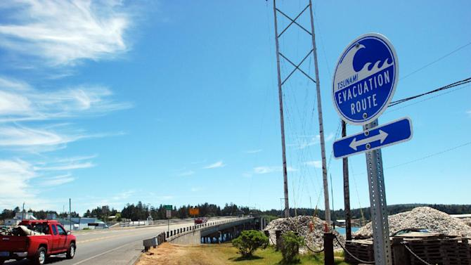 A sign points people to the evacuation route in case of a tsunami on Thursday, May 31, 2012 in Charleston, Ore. Authorities expected thousands of people to take park in a tsunami drill Thursday in the Oregon coastal communities of Charleston, Coos Bay and North Bend. (AP Photo/Jeff Barnard)