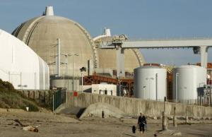 A woman and her dogs walk past the San Onofre Nuclear Generating Station that sits on the shore of the Pacific Ocean in North San Diego County