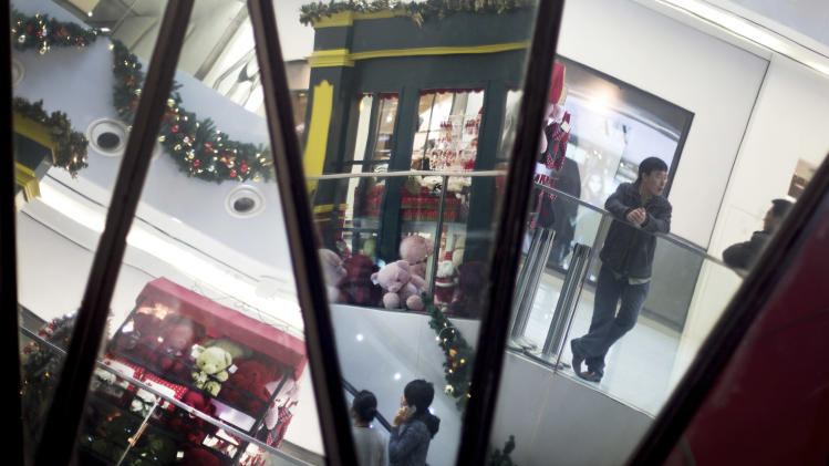 Chinese shoppers and Christmas decorations are reflected in mirrors inside a shopping mall in Beijing Monday, Dec. 10, 2012. China's trade weakened sharply in November, adding to challenges for the world's second-largest economy as a gradual recovery takes shape. Export growth plunged to 2.9 percent over a year earlier from the previous month's 11.6 percent, customs data showed Monday. Imports were flat, down from October's 2.4 percent growth. (AP Photo/Andy Wong)