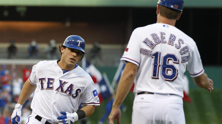 Texas Rangers base coach Dave Anderson (16) greets Rangers' Ian Kinsler as he rounds third on his solo home run off New York Yankees' Hiroki Kuroda in the first inning of a baseball game Tuesday, April 24, 2012, in Arlington, Texas. (AP Photo/Tony Gutierrez)