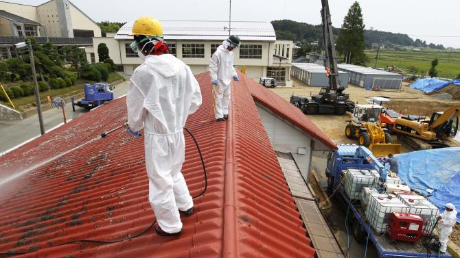 FILE - In this Aug. 18, 2011 file photo, workers in white radiation protective suits, go through an operation to decontaminate radiation from the roof of Yasawa Kindergarten in Minami-Soma, about 12 miles (20 kilometers) away from the tsunami-crippled Fukushima Dai-ichi nuclear facility, in Fukushima prefecture, northeastern Japan. Influential Japanese scientists who help set national radiation exposure limits have for years had trips paid for by the country's nuclear plant operators to attend overseas meetings of the world's top academic group on radiation safety. Some of these same scientists have consistently given optimistic assessments about the health risks of radiation, interviews with the scientists and government documents show. Their pivotal role in setting policy after the March 2011 tsunami and ensuing nuclear meltdowns meant the difference between schoolchildren playing outside or indoors and families staying or evacuating.  (AP Photo/Hiro Komae, File)