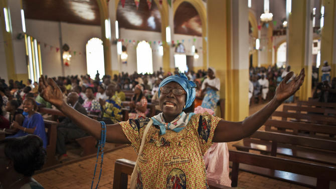 A churchgoer raises her hands as she sings in the New Year's Day morning mass at the Notre Dame Cathedral of the Immaculate Conception in Bangui, Central African Republic, Tuesday, Jan. 1, 2013. President Francois Bozize's government is coming under growing threat as rebels vowing to overthrow him rejected appeals from the African Union to hold their advance and try to form a coalition government. (AP Photo/Ben Curtis)