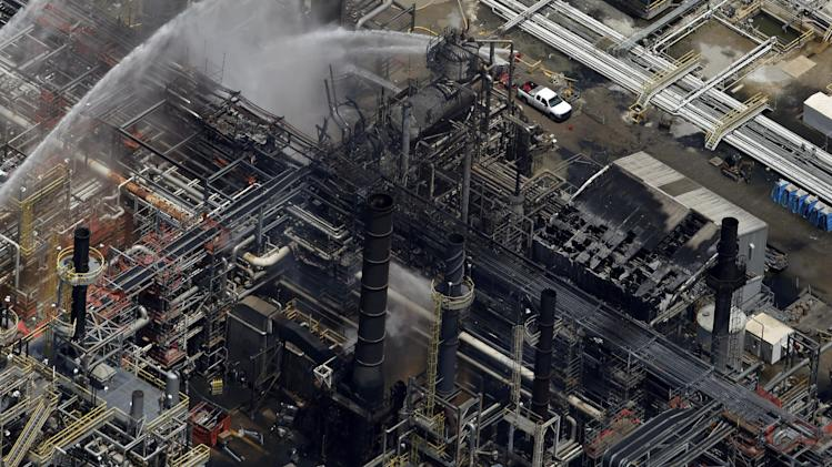 A chemical plant is hosed down after a fire in this aerial photo about twenty miles southeast of Baton Rouge, in Geismer, La., Thursday, June 13, 2013. The plant makes highly flammable gases that are basic building blocks in the petrochemical industry. (AP Photo/Gerald Herbert)