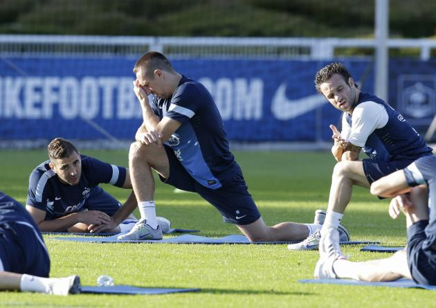 France's national soccer team players Karim Benzema, Franck Ribery and Mathieu Valbuena stretch during a training session in Clairefontaine