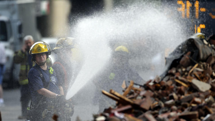 A firefighter sprays the debris in the aftermath of a building collapse, Thursday, June 6, 2013, in Philadelphia. On Wednesday, the building under demolition collapsed onto a neighboring thrift store, killing six people and injuring 14, including one who was pulled from the debris nearly 13 hours later. (AP Photo/Matt Rourke)