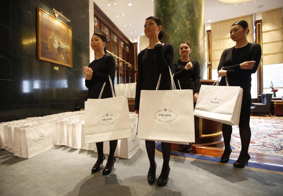 Staff members of Prada carry bags during a press conference in Hong Kong Sunday, June 12, 2011. Prada and its bankers say an international roadshow to promote the Italian fashion house's upcoming Hong Kong IPO is going well despite recent turmoil in world stock markets. Prada is selling some 423.3 million shares in an initial public offering this month. (AP Photo/Vincent Yu)