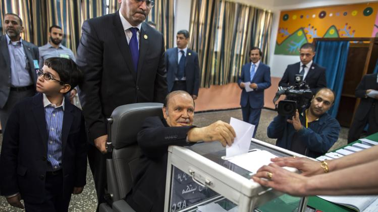 Algeria's President Abdelaziz Bouteflika (C) casts his ballot during the presidential election in Algiers