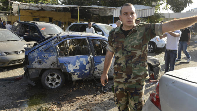 A Lebanese army officer stands next to a damaged car as he asks journalists to step back, at the scene where a rocket struck a car exhibit, at the Mar Mikhael district south of Beirut, Lebanon, Sunday May 26, 2013. Rockets slammed Sunday into two Beirut neighborhoods that are strongholds of Lebanon's Hezbollah group, wounding at least 4 people, Lebanese security officials and media said. Tensions have been running high in Lebanon, and Syrian rebels have threatened to retaliate against the militant Shiite Hezbollah group for sending fighters to assist President Bashar Assad's forces in Syria. (AP Photo/Ahmad Omar)