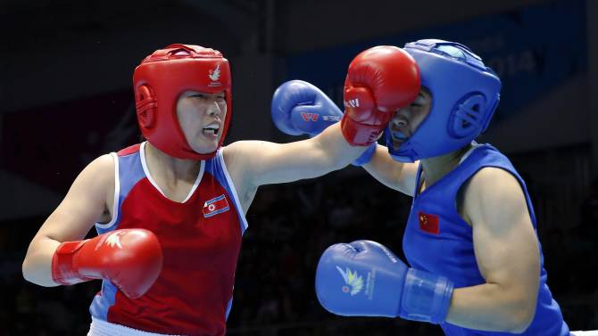 North Korea's Jang Un Hui fights with China's Li Qian during their women's middle (69-75kg) boxing match final at the Seonhak Gymnasium during the 17th Asian Games in Incheon