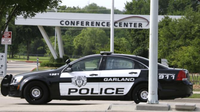 A Garland Police cruiser drives by the Curtis Culwell Center Tuesday, May 5, 2015, in Garland, Texas. A man whose social media presence was being scrutinized by federal authorities was one of two suspects in the Sunday shooting at this location that hosted a cartoon contest featuring images of the Muslim Prophet Muhammad. The Islamic State group on Tuesday claimed responsibility for the attack. (AP Photo/LM Otero)