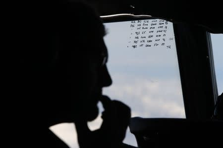 File photo of a crew member aboard a Royal New Zealand Air Force P-3K2 Orion aircraft alongside handwritten notes of other search craft in the area, during a search for the missing Malaysian Airlines MH370 over the Indian Ocean