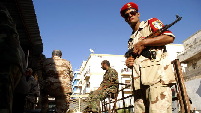 Libyan security forces stand guard as people turn in weapons in Benghazi, Libya, Saturday, Sept. 29, 2012. Hundreds of Libyans have converged on a main square in Benghazi in response to a call from the military to hand over their weapons, some driving in with armored personnel carriers, vehicles with mounted anti-aircraft guns and hundreds of rocket launchers. The call by the Libyan chiefs of staff was promoted on a private TV station earlier this month. But the call may have gained traction in the wake of the attack against the U.S. consulate in Benghazi in which the American ambassador and three staffers were killed. The attack was followed by a popular uproar against armed militias which have increasingly challenged government authorities. (AP Photo/Ibrahim Alaguri)