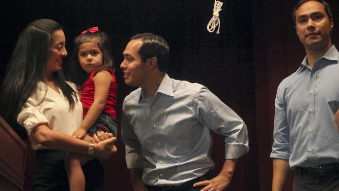 Mayor Julian Castro, center, stands with his wife, Erica Castro, their daughter, Carina, 3, and his brother, Joaquin Castro, right, on stage during the send-off party for their trip to the Democratic National Convention at the St. Paul Community Center in San Antonio on  Sept. 1, 2012. Castro delivers the convention's keynote address Tuesday, a nod to the importance of Hispanic voters in the race.  (AP Photo/San Antonio Express-News, Lisa Krantz)