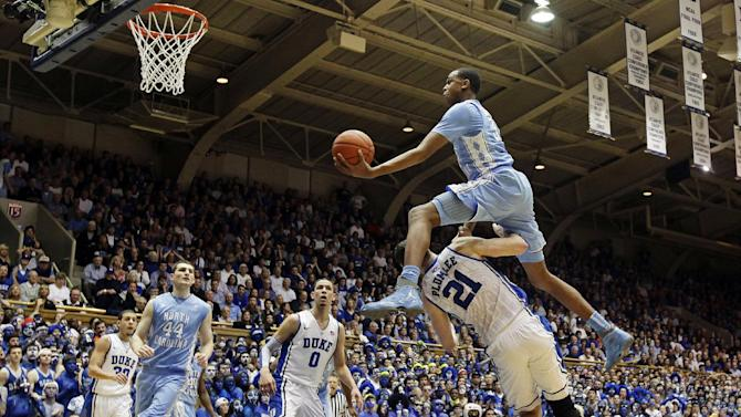 North Carolina's John Henson jumps over Duke's Miles Plumlee (21) for a shot during the first half of an NCAA college basketball game in Durham, N.C., Saturday, March 3, 2012. At rear, Duke's Seth Curry and Austin Rivers (0) watch with North Carolina's Tyler Zeller (44). (AP Photo/Gerry Broome)