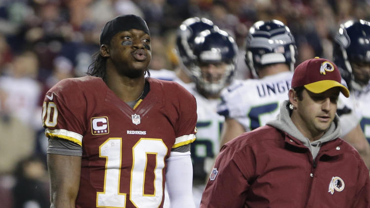 Washington Redskins quarterback Robert Griffin III walks off the field after twisting his knee during the second half of an NFL wild card playoff football game against the Seattle Seahawks in Landover, Md., Sunday, Jan. 6, 2013. (AP Photo/Evan Vucci)