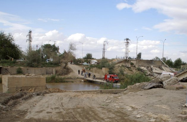 People cross the river on a makeshift bridge after a bridge was destroyed by shelling, in Deir al-Zor