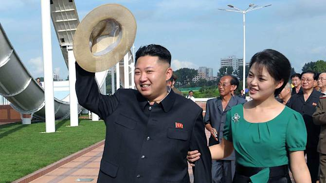 """FILE - In this July 25, 2012 file photo released by the Korean Central News Agency and distributed in Tokyo by the Korea News Service, North Korean leader Kim Jong Un, accompanied by his wife Ri Sol Ju, waves to the crowd as they inspect the Rungna People's Pleasure Ground in Pyongyang, North Korea. The online version of China's Communist Party newspaper has hailed a report by The Onion naming Kim as the """"Sexiest Man Alive"""" - not realizing it is satire. The People's Daily on Tuesday, Nov. 27, 2012 ran a 55-page photo spread on its website in a tribute to the round-faced leader, under the headline """"North Korea's top leader named The Onion's Sexiest Man Alive for 2012."""" (AP Photo/Korean Central News Agency via Korea News Service, File)"""