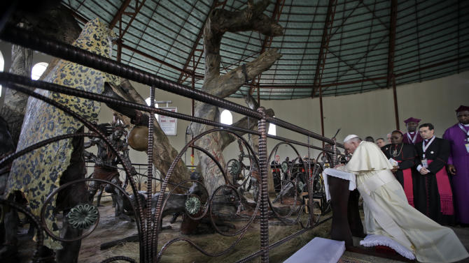 Pope Francis kneels in prayer during his visit at the Anglican martyrs' shrine of Namugongo, Kampala, Uganda, Saturday, Nov. 28, 2015. Pope Francis is in Africa for a six-day visit that is taking him to Kenya, Uganda and the Central African Republic. (AP Photo/Andrew Medichini, Pool)