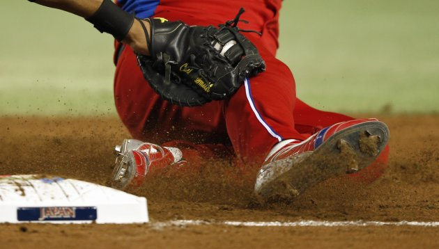 Cuba's first base runner Cepeda is tagged out by Netherlands' first baseman Smith at the WBC second round game in Tokyo